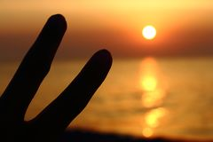 Victory finger`s sign against sunset by the sea. Finger`s gesture means victory against sunset by the sea. Happiness and freedom sign. Vacation by the seaside Royalty Free Stock Photos