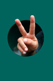 Victory hand. Hand coming out through a round hole Royalty Free Stock Photos