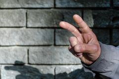 Victory hand sign. Gesture mens hand of two fingers. Concept of positive, peace, win. Closeup view on gray stone wall background. royalty free stock image