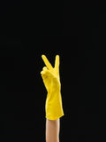 Victory. Hand up with yellow protective glove showing victory sign, on black background Stock Photo