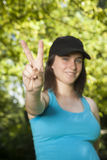 Victory hand young woman. Pregnant young woman with blue shirt victory hand gesture over green trees background street Stock Images