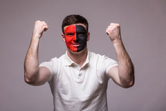 Victory, happy and  goal scream emotions of Albanian football fan in game support of Albania national team on grey background. Stock Photo