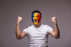Victory, happy and  goal scream emotions of Romanian football fan in game support of Romania national team on grey background. Stock Image