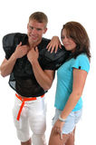 Victory Hug. A pretty girl snuggles up to a football player after the game Royalty Free Stock Photos