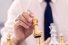 Victory leader and success concept, business man playing take a checkmate figure another king with team on the chess board and royalty free stock image