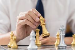 victory leader and success concept, business man playing take a checkmate figure another king with team on the chess board and stock images