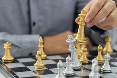 victory leader and success concept, business man playing take a checkmate figure another king with team on the chess board and stock image