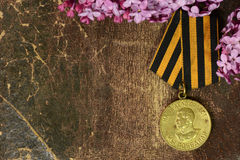 Victory medal after the Second World War in lilac flowers Royalty Free Stock Images