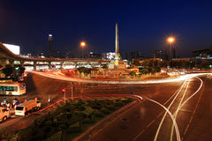 Victory monument with light trail on street in Bangkok Stock Photos