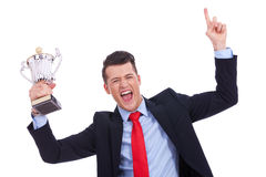 Victory roar of a young businss man. With a big trophy cup on white background royalty free stock photography