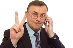 Victory sign. Businessman with cell phone gesturing victory sign Royalty Free Stock Images