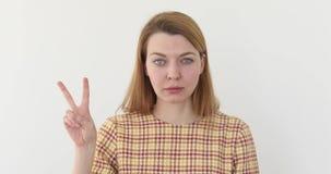 Victory Sign av den härliga unga kvinnan, stående arkivfilmer