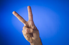 Victory sign on blue background Stock Images