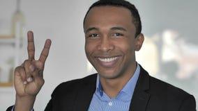 Victory Sign pelo homem de negócios afro-americano ocasional positivo filme