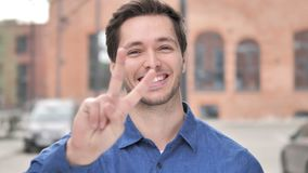 Victory Sign by Positive Young Man Standing Outdoor. 4k high quality, 4k high quality stock video footage