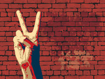 The Victory sign with red brick wall background. Royalty Free Stock Photography