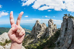Victory sign on top of the background cleared up in the mountain Stock Image