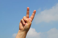Victory or peace sign with two fingers. A two finger victory or peace sign with a blue sky background royalty free stock images