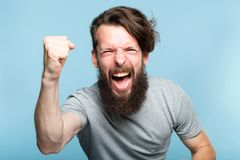 Victory success win gesture excited agitated man. Victory success and achievement. excited thrilled agitated guy making a win gesture. hipster man portrait on royalty free stock photo