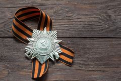 Victory symbol, St. George ribbon and order on wooden background stock photo
