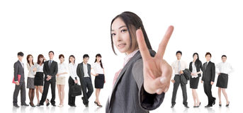 Victory team. Attractive Asian business women give you a victory sign and stand in front of her team Stock Photography