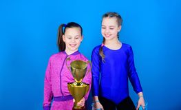 Victory of teen girls. Acrobatics and gymnastics. Little girls hold jump rope. Winner in competition. Sport success. Happy children with gold champion cup stock image