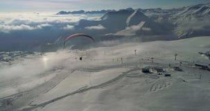 Vidéo aérienne étonnante de paraplane aux montagnes de neige Bourdon en gros plan des montagnes du ` s d'hiver de paraglide banque de vidéos