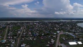 Vidéo aérienne un petit village à l'arrière-plan de la forêt et du lac Panorama du tir de village sur le bourdon clips vidéos