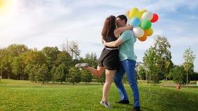 Vidéo animée lente de beaux jeunes couples dans l'amour ayant l'amusement avec des ballons et l'embrassant au parc banque de vidéos