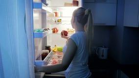 Vidéo animée lente de belle jeune femme prenant la pomme fraîche du réfrigérateur la nuit Concept de la nutrition saine clips vidéos