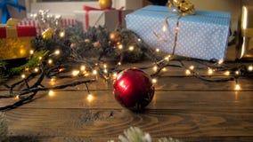 Vidéo animée lente du roulement rouge de babiole de Noël sur la table en bois clips vidéos