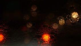 Vidéo de belle lumière trouble colorée du trafic dehors sur la route Écoulements et essuie-glace de pluie sur le verre de pare-br banque de vidéos