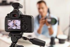 Vidéo de enregistrement de blogger de photo à l'intérieur, foyer sélectif sur l'affichage de caméra photographie stock libre de droits