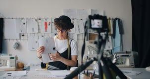 Vidéo de enregistrement de concepteur féminin de blogger pour le vlog d'Internet montrant des croquis clips vidéos