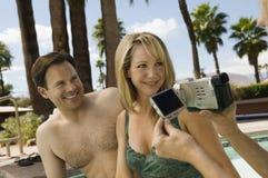 Vidéo de femme attachant du ruban adhésif à des couples par la piscine. Photos stock