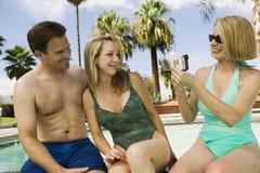 Vidéo de femme attachant du ruban adhésif à des couples par la piscine Photo libre de droits