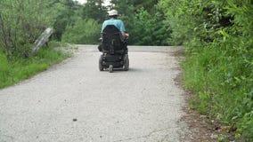 vidéo de la résolution 4k d'un homme sur le fauteuil roulant électrique chassant la route en nature banque de vidéos