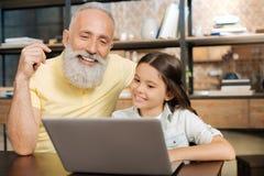 Vidéo de observation avec du charme de grand-père et de petite-fille sur l'ordinateur portable Photographie stock