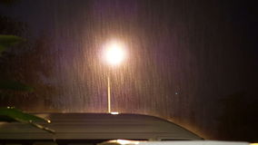 Vidéo de pleuvoir lourd la nuit sur le parking de voiture clips vidéos