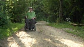 vidéo de portrait de la résolution 4k d'un homme handicapé dans un fauteuil roulant électrique en nature banque de vidéos