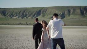 Vidéo de tir de vidéographe avec le steadicam La jeune belle jeune mariée dans une robe l'épousant va chez le marié Réunion de banque de vidéos