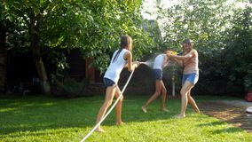 vidéo 4k de la jeune famille heureuse ayant le combat de l'eau au jour ensoleillé chaud dans le jardin banque de vidéos