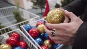 vidéo 4k des mains femelles avec le rouge et les boules d'or La fille choisit des jouets de nouvelle année banque de vidéos