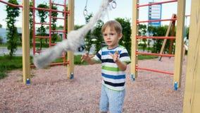 vidéo 4k du petit garçon de sourire de garçon jouant avec la corde pour s'élever sur le terrain de jeu au parc clips vidéos