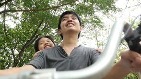 vidéo 4K : Petit enfant asiatique faisant un cycle avec le père banque de vidéos