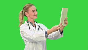 Vidéoconférence naving de jeune docteur heureux sur le comprimé avec le patient sur un écran vert, clé de chroma banque de vidéos