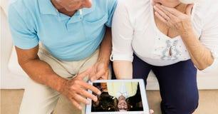 Vidéoconférence supérieure de couples sur la tablette photographie stock libre de droits