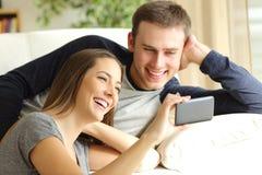 Vidéos de observation de couples heureux dans un téléphone Images stock