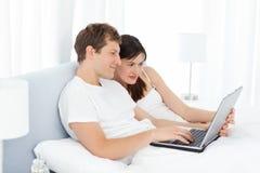 Vidéos de observation de jeunes couples sur leur ordinateur Image libre de droits