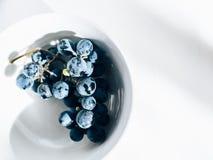 Vid de uva del Merlot en el cuenco blanco de la porcelana en la tabla blanca Fotografía de archivo